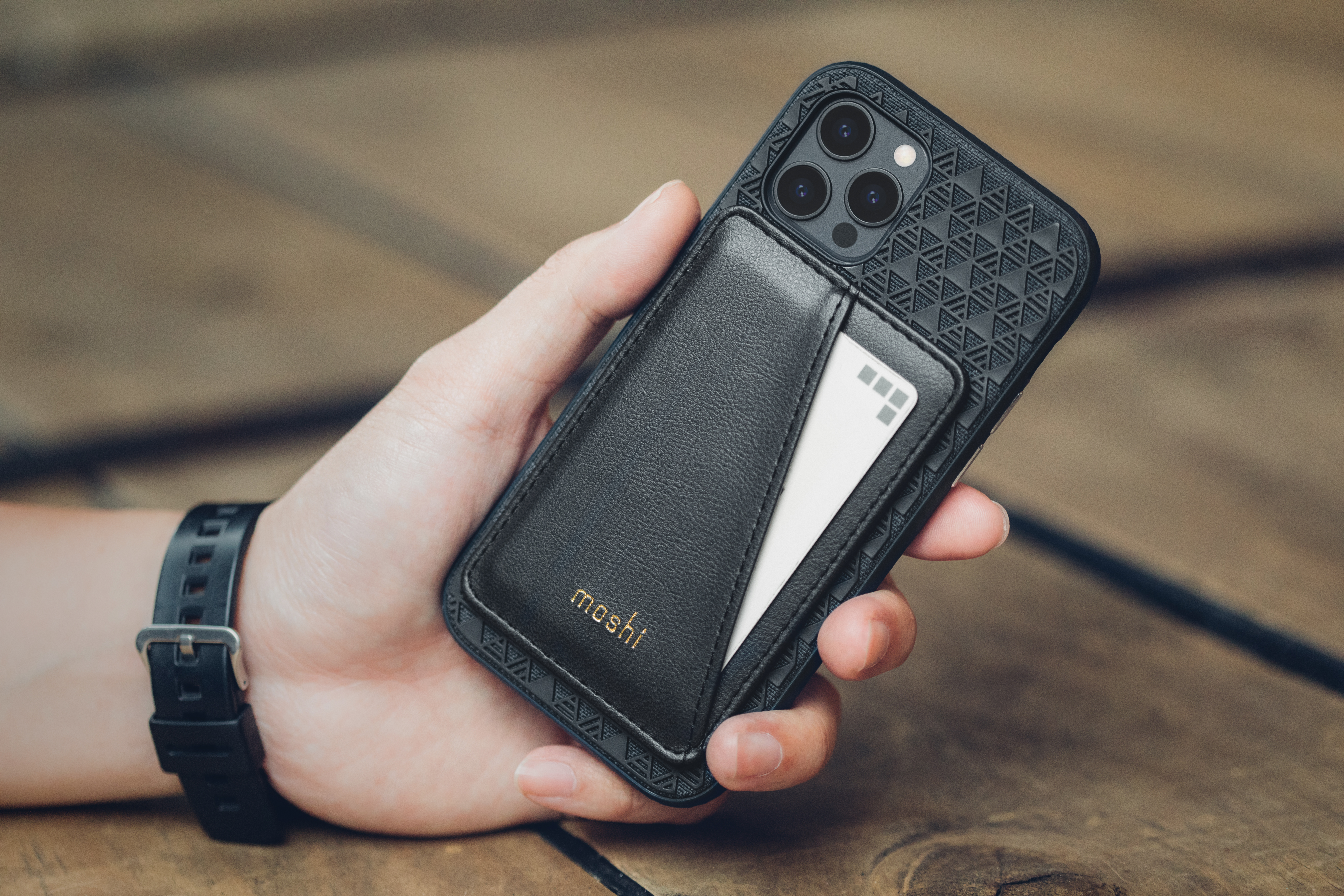 A hand holding a smartphone with the SnapTo Slim Wallet attached